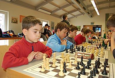 Kinder blicken angestrengt auf das Schachbrett